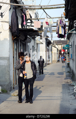 Two young local men walk down an alleyway in the old town district of Suzhou, China