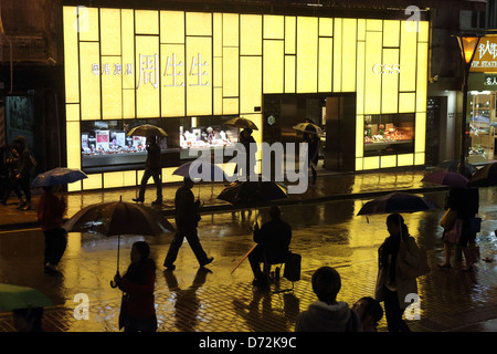 Hong Kong, China, people at night in the rain outside a jeweler Business CSS - Stock Photo