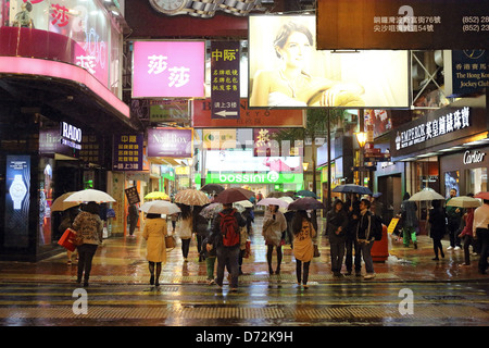 Hong Kong, China, people in rain in Causeway Bay district at night - Stock Photo