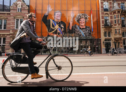 Netherlands, Amsterdam, 27 April 2013.A cyclist passes by portraits of Queen Beatrix of the Netherlands and her - Stock Photo