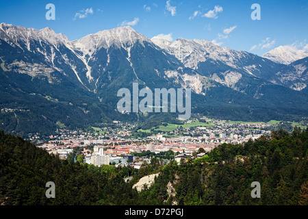 Innsbruck Austria sits in a valley below the Alps. - Stock Photo