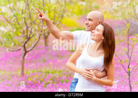 Attractive guy showing something in sky his lovely girlfriend, having fun in spring park, relaxation outdoors, romantic - Stock Photo
