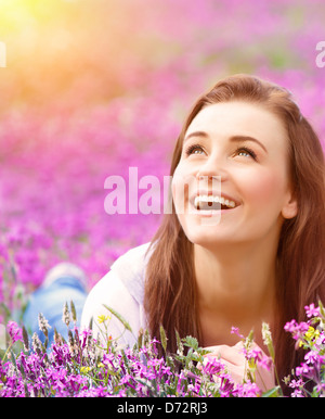 Closeup portrait of beautiful female laying down in fresh pink floral field, warm sunset light, spring nature - Stock Photo