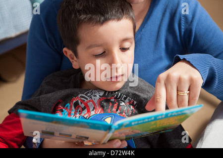 Mother teaches child to read - Stock Photo