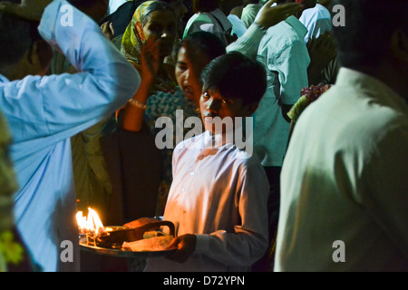 boy with fire, giving blessings in temple - Stock Photo