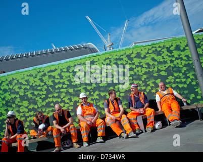Seven workers wearing orange high visibilty saftey clothing taking a break on Kings Boulevard, Kings Cross, London - Stock Photo