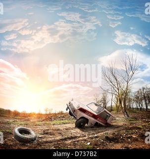 Car on a dump against an evening sunlight - Stock Photo