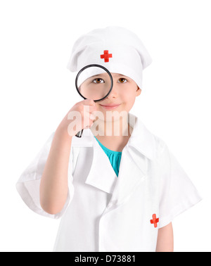 Portrait of a smiling little girl wearing as a nurse on white uniform and holding in right-hand a magnifying glass - Stock Photo