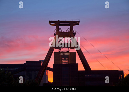 colourful sunset at the winding tower of shaft 12 at Zollverein Coal Mine Industrial Complex in Essen, North Rhine - Stock Photo