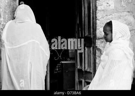 Women in white veils stand at the entrance to the Ethiopian Chapel at the Church of The Holy Sepulchre. Jerusalem, - Stock Photo