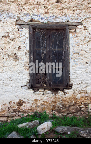 Old window with ornate iron grille in weathered stone house front - Stock Photo