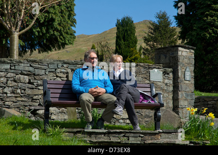 Middle-aged couple relaxing on a bench in Ambleside, Lake District National Park, Cumbria, England UK - Stock Photo