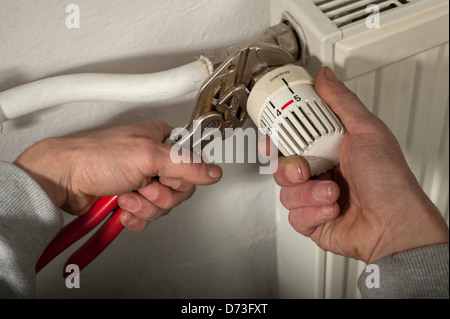 Berlin, Germany, a craftsman screw valve on the thermostat of a radiator - Stock Photo
