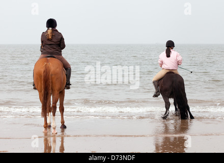 Two young women on horses riding on the beach at the waters edge Holkham Beach Norfolk UK - Stock Photo