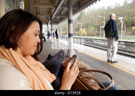 A young woman using her mobile phone on a station platform waiting for a train, London UK - Stock Photo