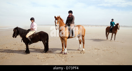 Three young women riding  horses at Holkham beach in spring, North Norfolk coast, UK - Stock Photo