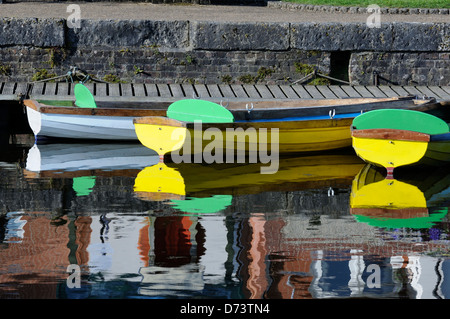 three bright and colourful colorful rowing boats tied moored to a pontoon jetty on a canal - Stock Photo