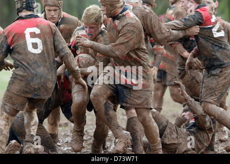 Teams battle in the mud during a game at the annual Cherry Blossom Rugby Tournament. - Stock Photo
