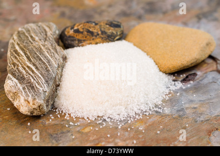 Closeup horizontal photo of coarse salt on a rock surface with rough rocks in background - Stock Photo