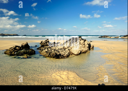 Rocks and pools at low tide on a sandy beach - Stock Photo