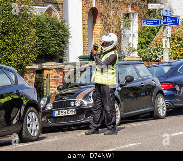 A traffic warden issues a ticket (PCN) for an illegally parked car - Stock Photo