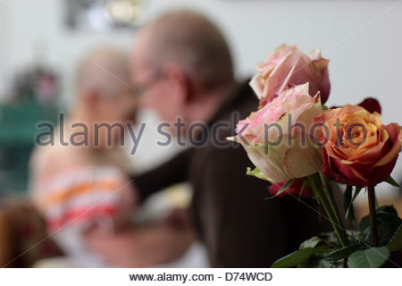 Roses with a man cleaning the body of his ill mother in the background - Stock Photo