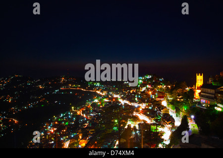 Houses on a hill lit up at night, Shimla, Himachal Pradesh, India - Stock Photo