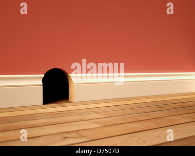 Mouse hole in a skirting board / baseboard - Stock Photo