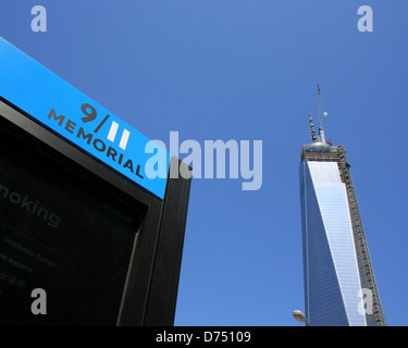 Entrance to the National 9/11 Memorial.  World Trade Center Tower One under construction in the background. - Stock Photo