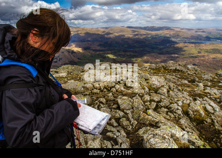 Woman hiker person taking a compass bearing from a paper map in the mountains, Old Man of Coniston horseshoe, Lake - Stock Photo