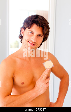 Man applying a tobacco control patch. - Stock Photo