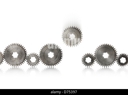 A row of old metallic cog gears being filled with one blurry falling gear. - Stock Photo
