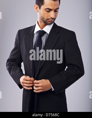 Portrait of a stylish businessman buttoning his suit - Stock Photo