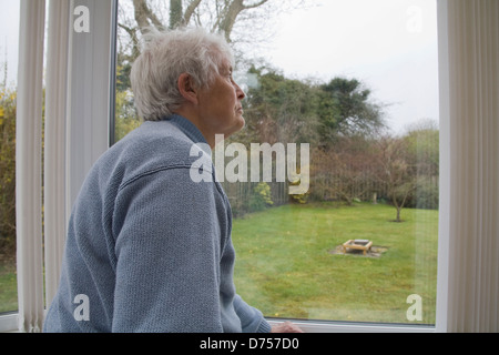UK Elderly woman staring out of conservatory window on a cold and wet day - Stock Photo