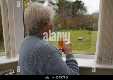 UK Elderly woman looking out of conservatory window drinking a hot drink on a cold and wet day decaffinated tea - Stock Photo