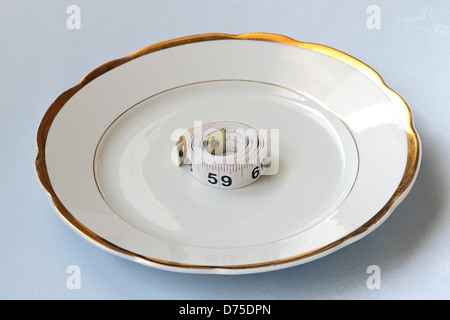 Roll of white centimeter on white china ware - Stock Photo