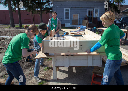 Volunteers build raised boxes for a community garden - Stock Photo
