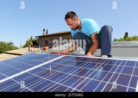 Torre Alfina, Italy, installing a solar power system on the roof of a detached house - Stock Photo