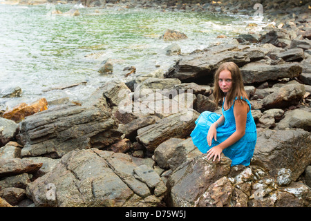 Teen-girl in a blue dress in the rocks of the coast. - Stock Photo