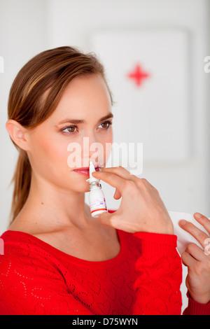 Woman using nasal spray for controlling rhinitis. - Stock Photo