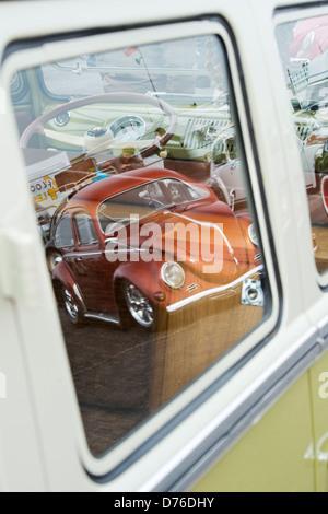 VW Beetle car reflected in the window of a VW Volkswagen camper van - Stock Photo