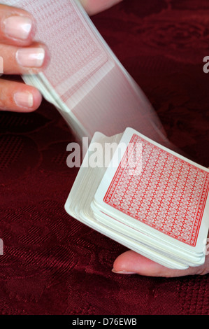 Woman shuffling a pack of playing cards showing card movement. - Stock Photo