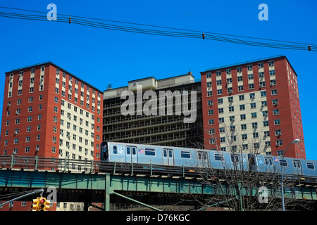A New York City subway train on an elevated track passes an apartment building in Coney Island, Brooklyn, New York - Stock Photo