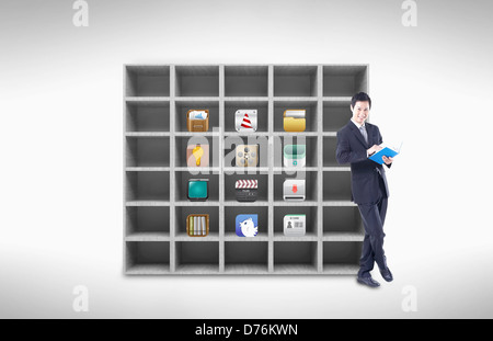 a businessman standing next to a book shelf with app icons inside - Stock Photo
