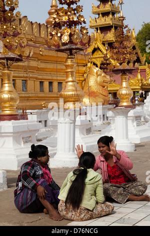 Three women chatting at the Shwezigon Pagoda in Bagan, Myanmar - Stock Photo