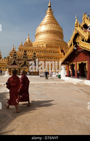Two monks walking at the Shwezigon Pagoda in Bagan, Myanmar - Stock Photo