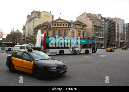 Taxi and Barcelona open top tourist bus - Stock Photo