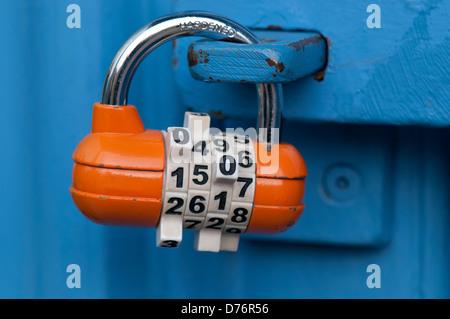 Orange combination padlock on blue door - Stock Photo