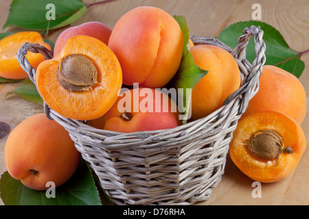 fresh apricot in wicker basket on wooden background - Stock Photo