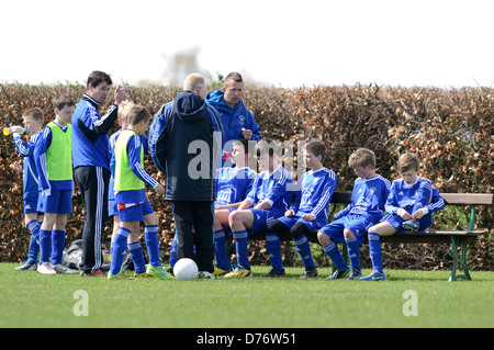 Junior boys football match action Uk - Stock Photo